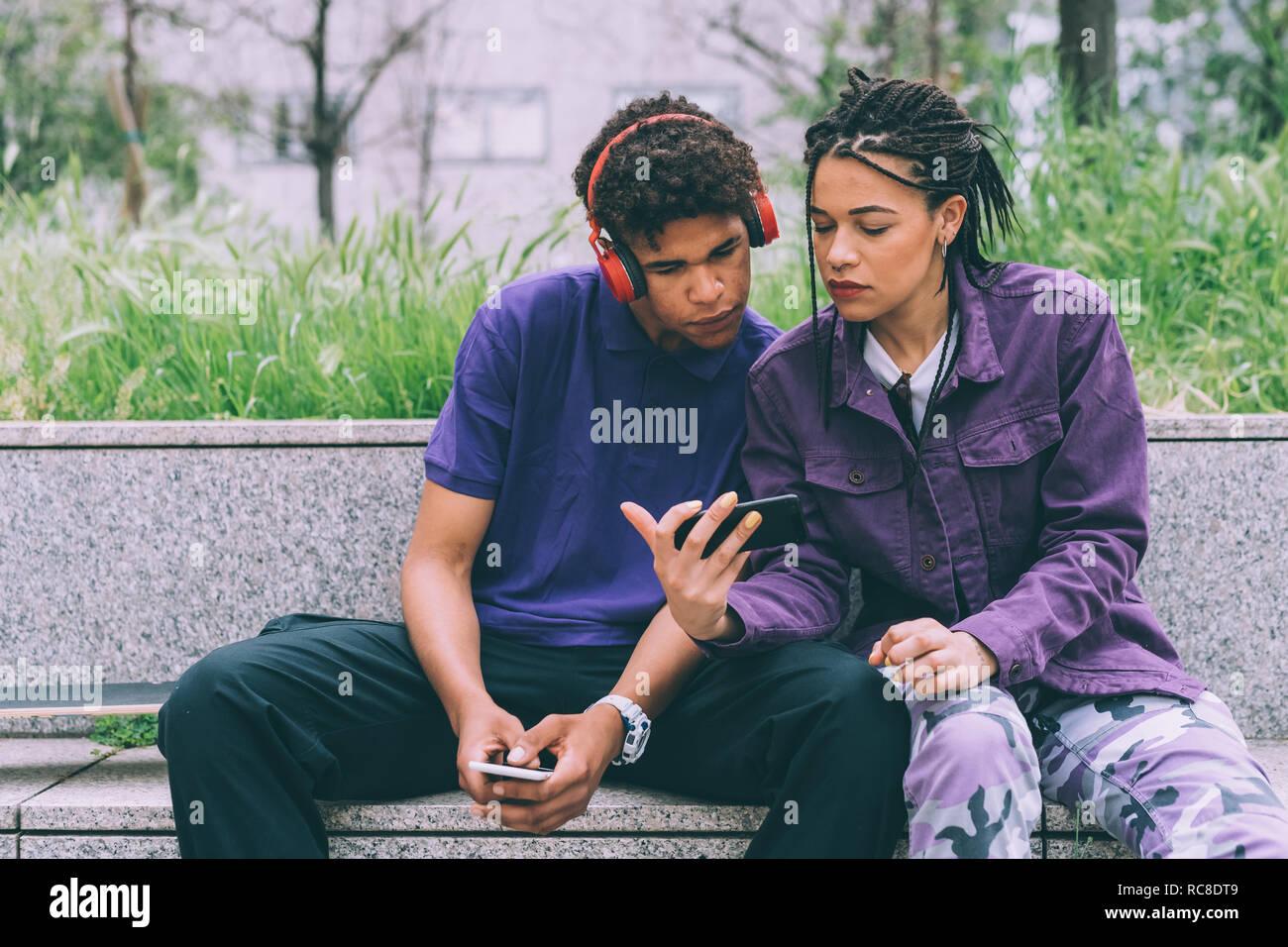 Frère et sœur d'observer sur l'ensemble mobile, Milan, Italie Banque D'Images