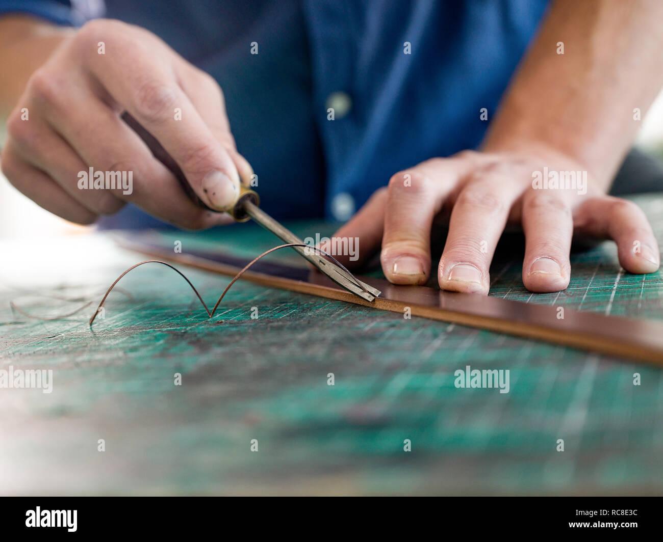 Leatherworker en cuir de fraisage pour sac bracelet en atelier, Close up of hands Banque D'Images