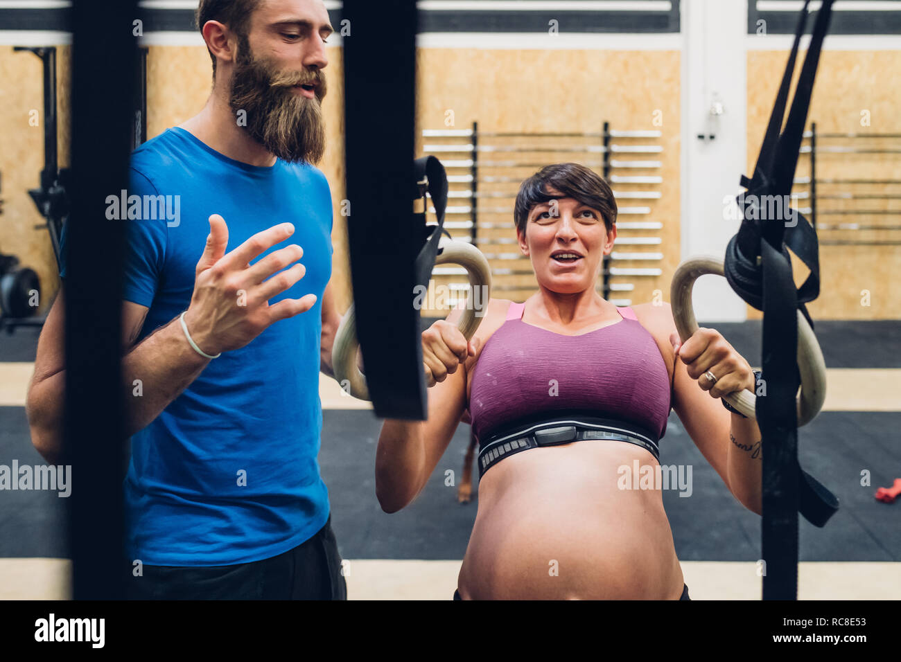 Directeurs formateur femme enceinte en utilisant l'équipement d'exercice dans la salle de sport Banque D'Images
