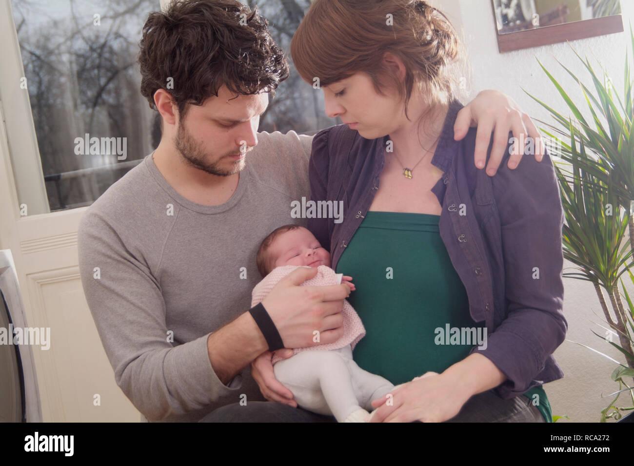 Junge Die Eltern halten ihre Tochter neugeborene im Arm, das ist genre 12 Tage alt   jeunes parents tenant son bébé nouveau-né dans ses bras - le bébé 12 ist Banque D'Images