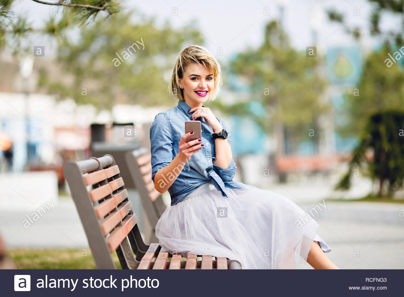 jeune fille blonde aux cheveux courts assise sur un banc. Black Bedroom Furniture Sets. Home Design Ideas