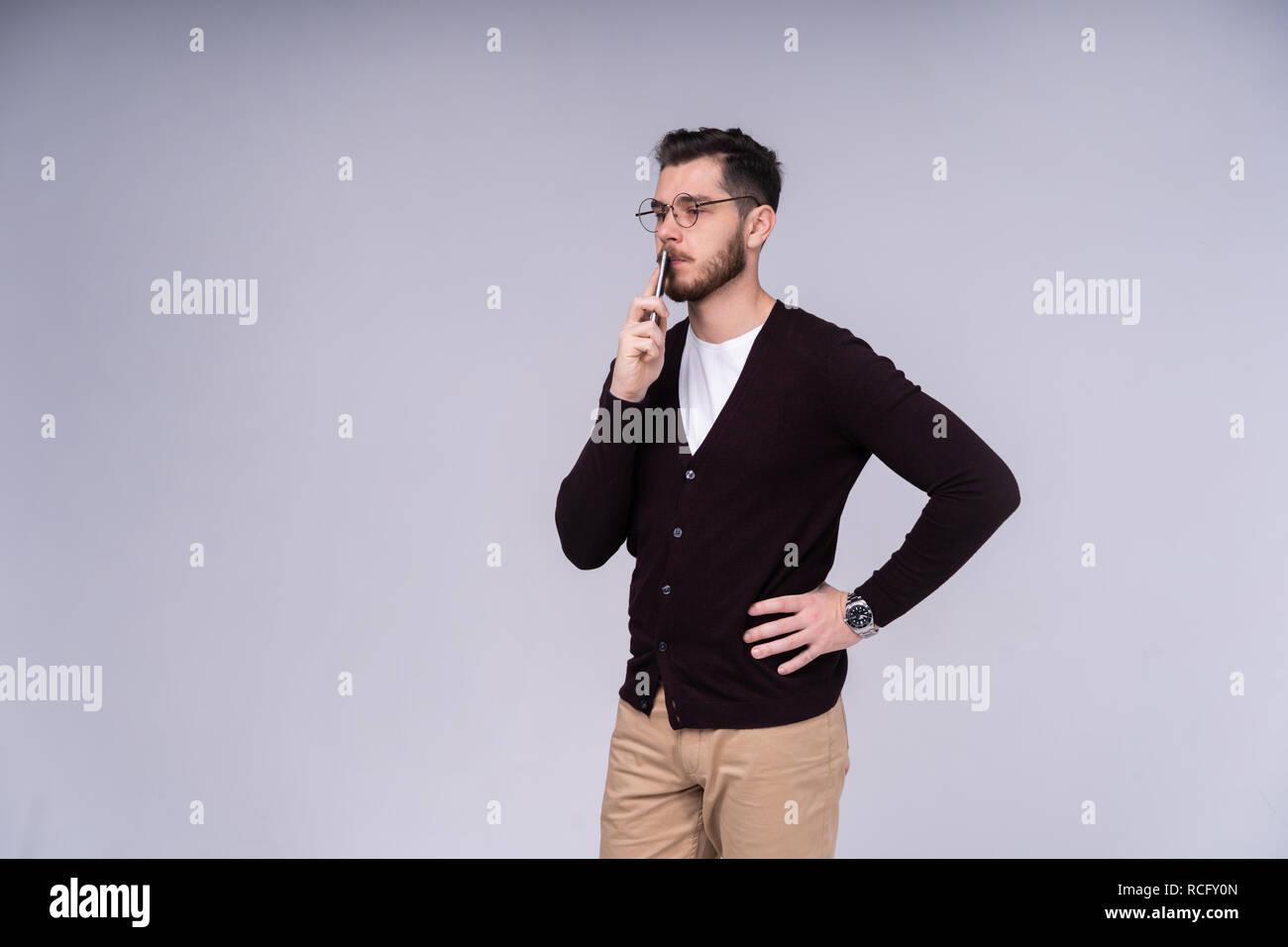Jeune homme séduisant sur fond gris. Photo Stock