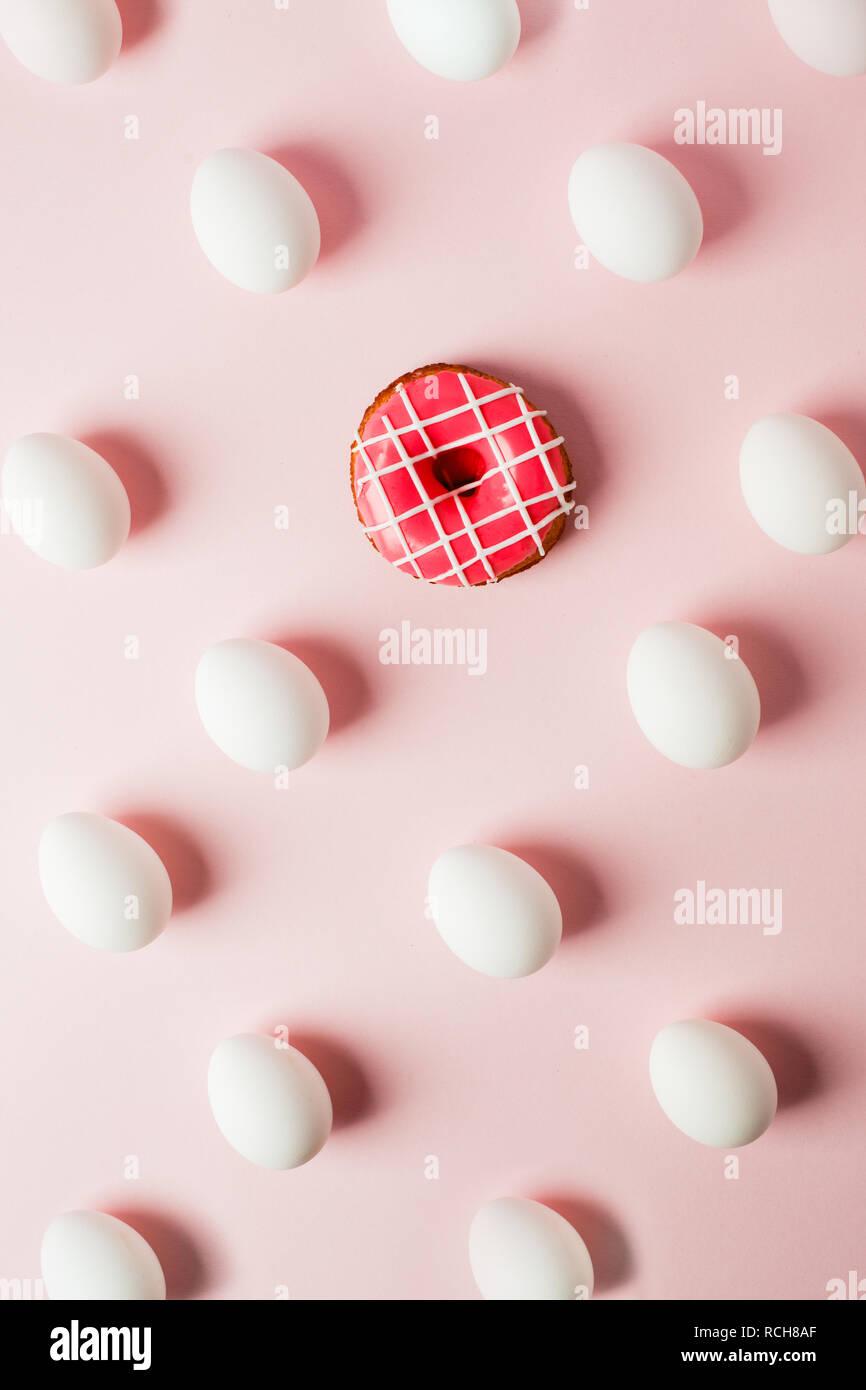 Pâques oeufs blancs de l'ombre et de répétition donut rose rose sur fond pastel, erreur système Photo Stock