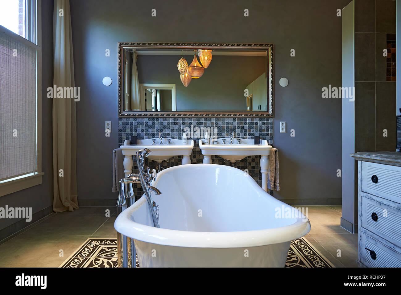 Une baignoire îlot dans une salle de bains design, classique ...