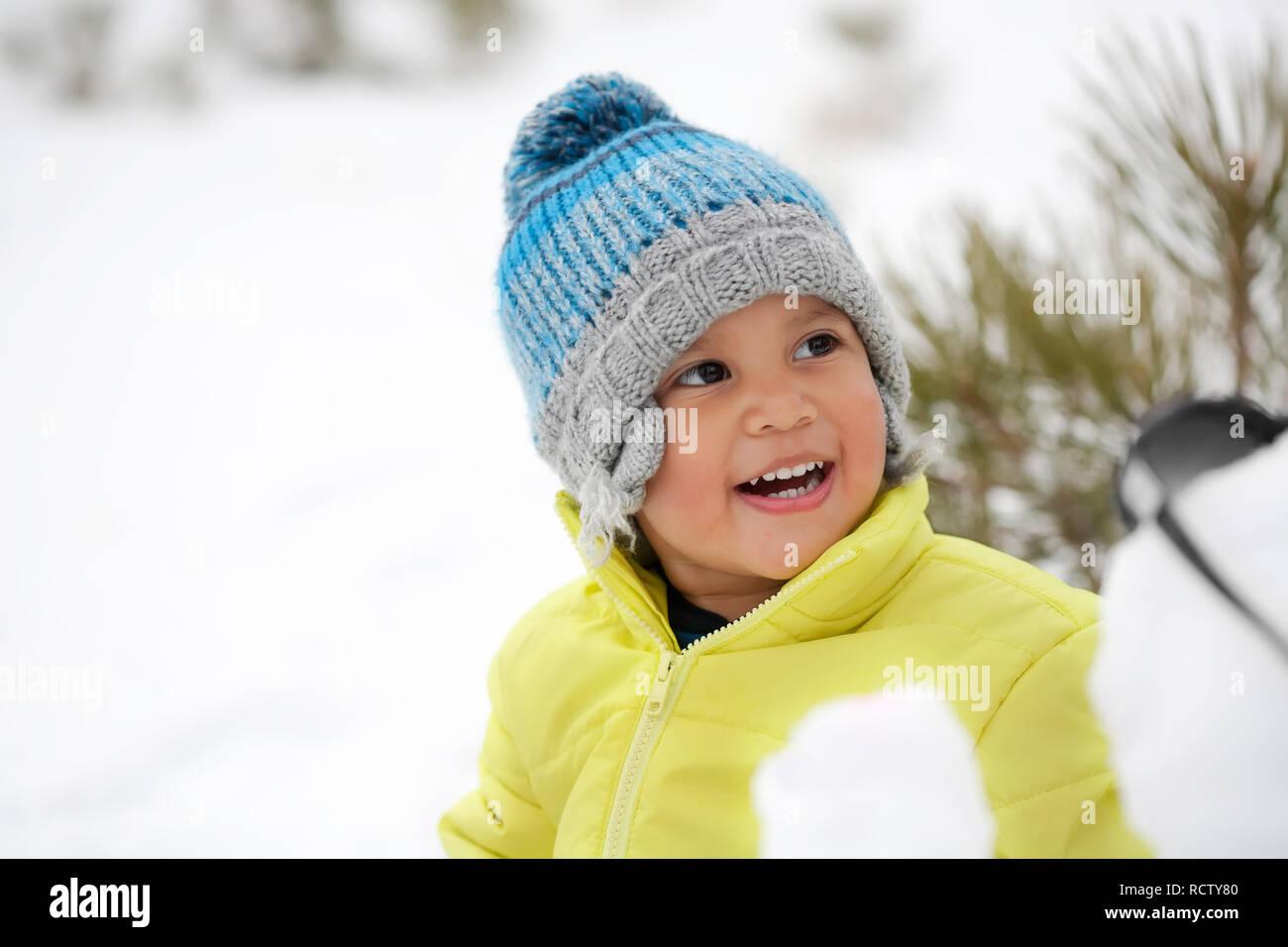 dca293cc49859 Rire bébé garçon portant des vêtements d'hiver dans une montagne couverte de  neige.