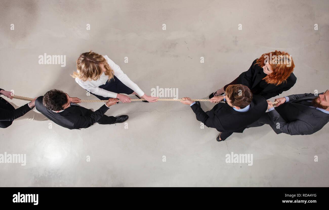 Homme et femme d'affaires rivales en compétition pour la commande en tirant la corde Photo Stock