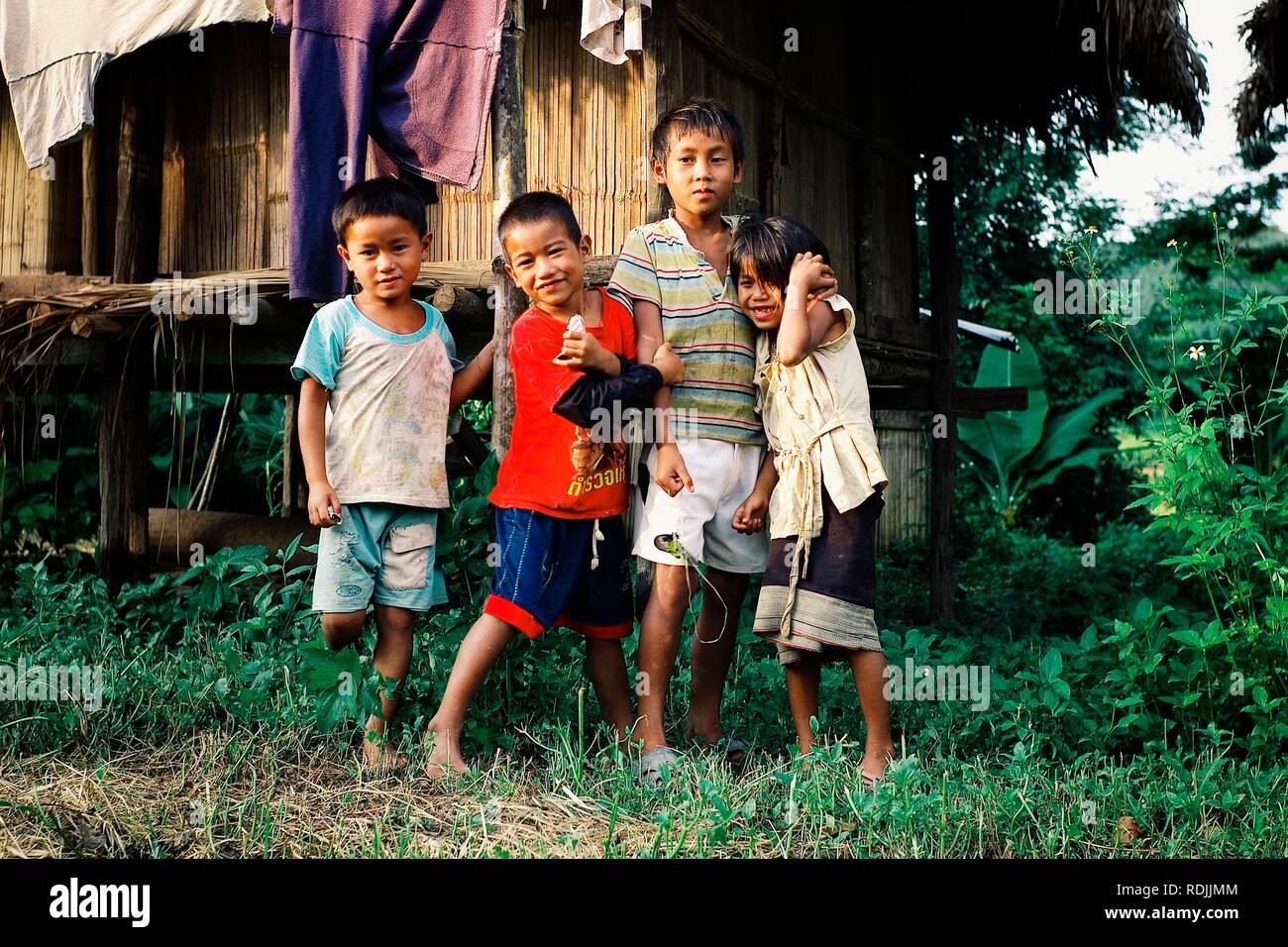 Luang Namta / Laos - 06 juil 2011: Enfants attendant à l'extérieur de leur maison de style cabane en bambou Banque D'Images