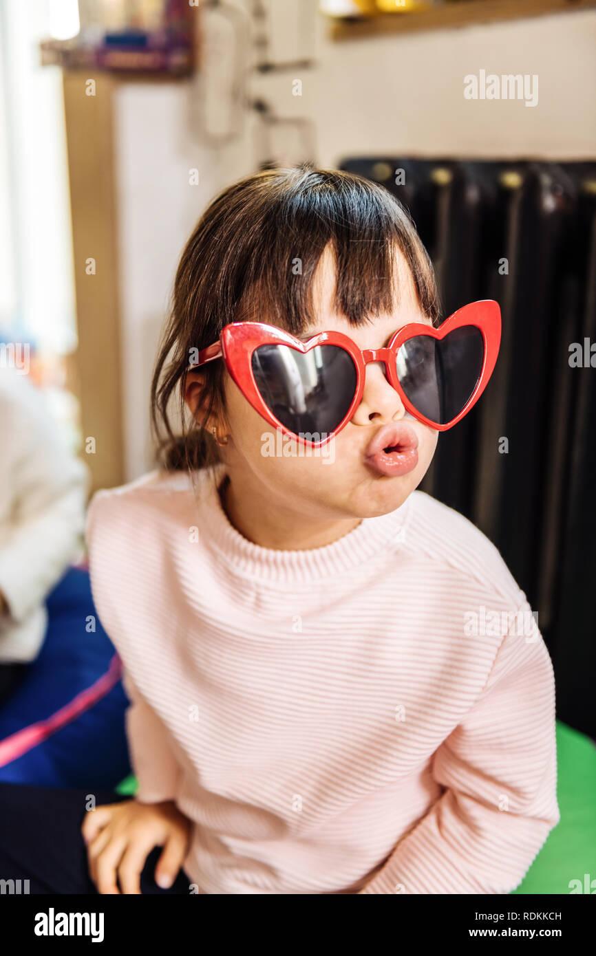00bd46b949 Petite fille aux cheveux noirs portant des lunettes de soleil en forme de  coeur rouge vif
