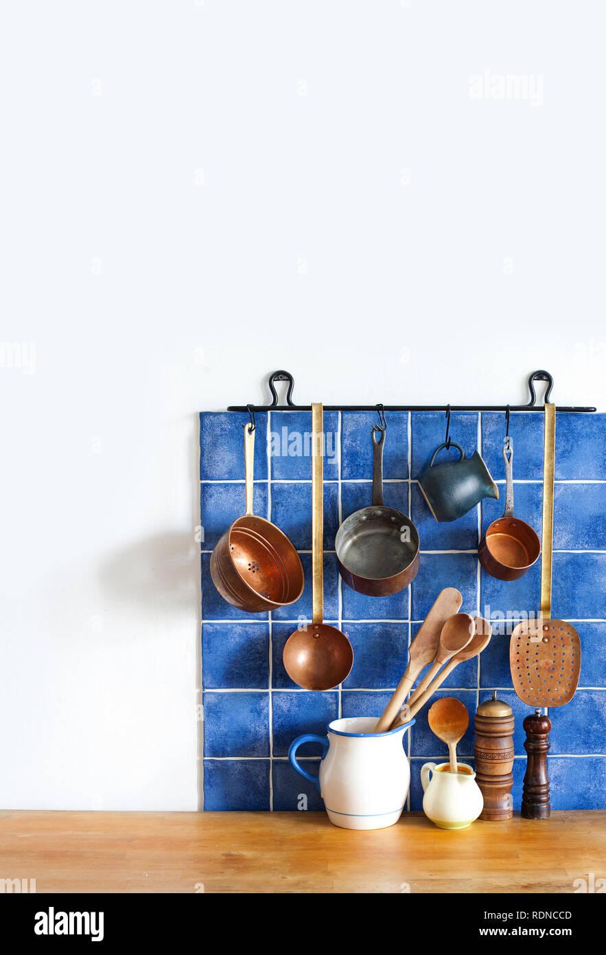 Intérieur de cuisine avec des ustensiles en cuivre vintage ancien style de cuisine Ustensiles. jeu. Casseroles, cuisine, cuillère écumoire hanging on blue tile wall. Copie espace, fond blanc. Photo Stock
