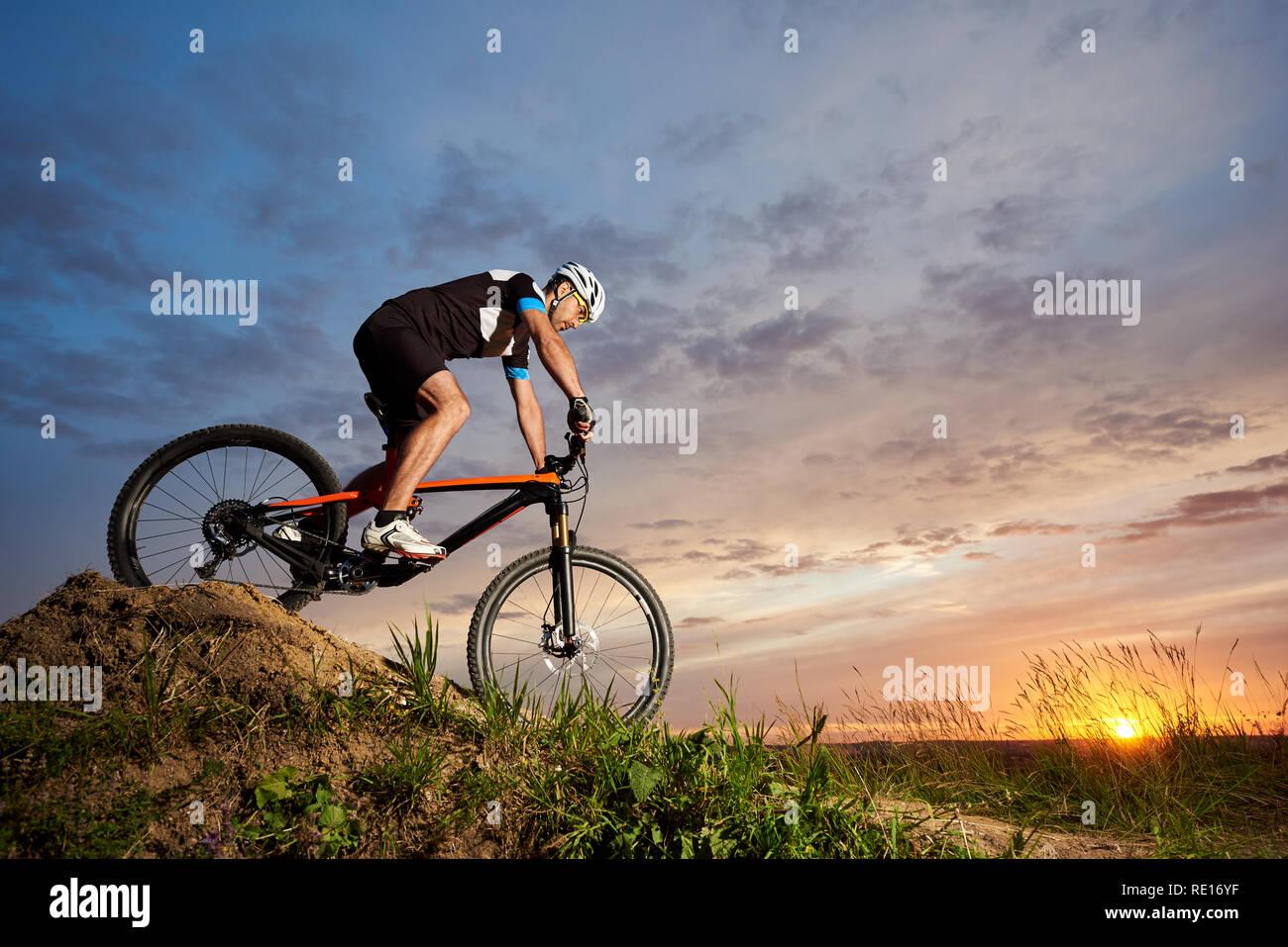 Cycliste actif portant des casques de sport et d'équitation, location de matériel roulant seul et en bas de la colline. L'homme robuste et sportive cyclisme contre beau coucher de soleil et rose-bleu fond de ciel. Photo Stock