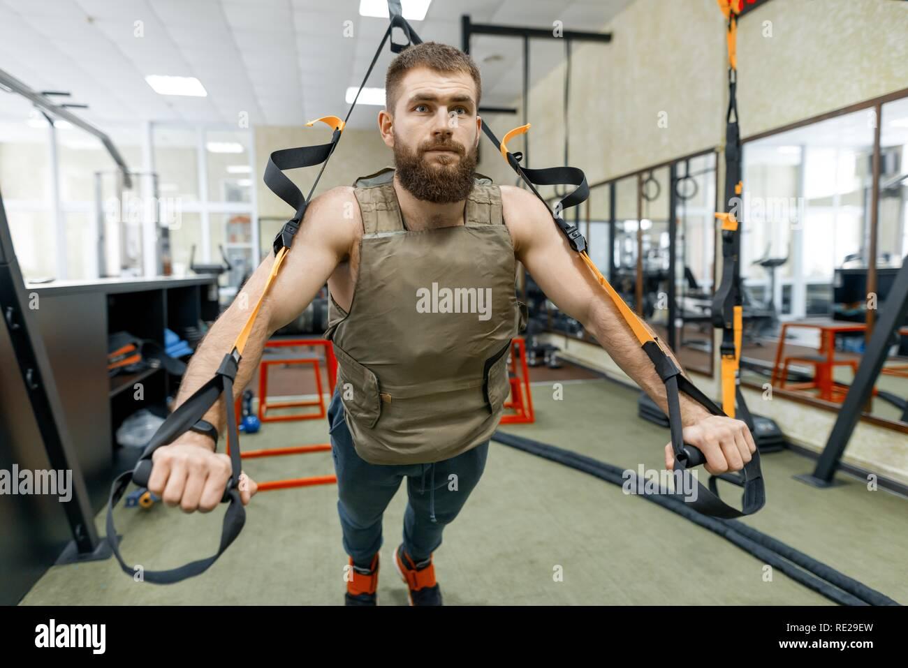 Homme barbu musclé habillé en veste militaire blindés pondérée de faire les exercices à l'aide de sangles de systèmes dans la salle de sport. Le sport, la formation, le culturisme et guérir Photo Stock