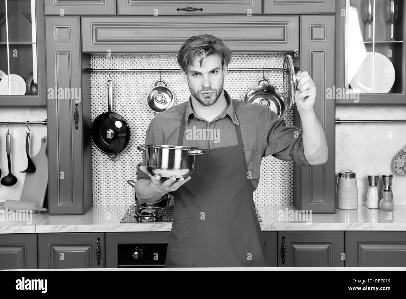 Maintenez l'homme Cook casserole et couvercle en cuisine. Batterie de cuisine, ustensiles de cuisine, de l'outil. Avec marmite macho pour ragoût, soupe plats. Cuisine traditionnelle, la cuisine, la préparation des aliments. Plats, menu recettes Photo Stock