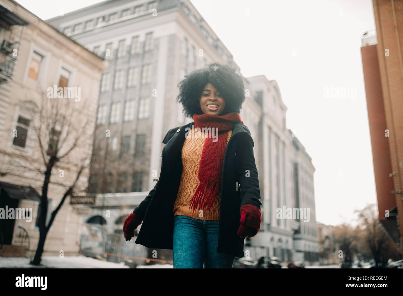Heureux jeune femme noire est à pied de la rue et de sourire. Libre. Banque D'Images