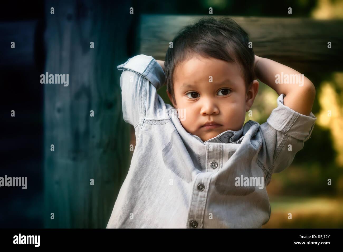 Jeune bébé garçon qui semble troublé, inquiet, ou d'exprimer des comportements sociaux tout en maintenant sa tête avec ses bras. Banque D'Images