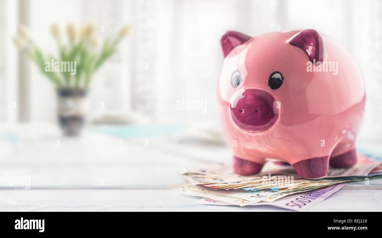 Tirelire Comité permanent sur les billets en euros sur la table dans l'intérieur de la famille. Le concept de la banque, assurance et services financiers pour les membres de la famille et hous Banque D'Images