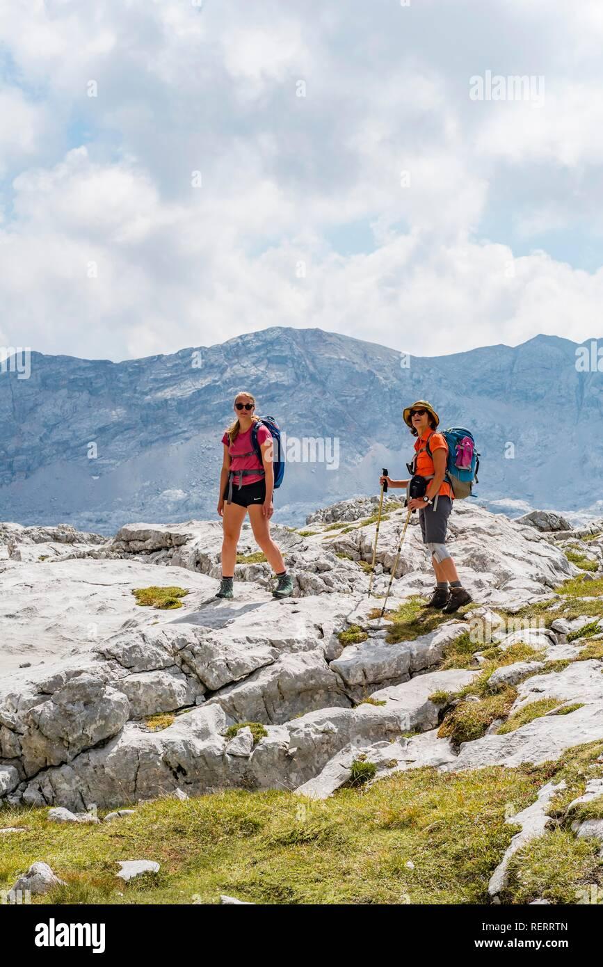 Deux randonneurs se pencher sur l'appareil photo, paysage de montagne, Stuhlgraben Hinterten Grießkogel,, Steinernes Meer, Funtenseetauern Banque D'Images