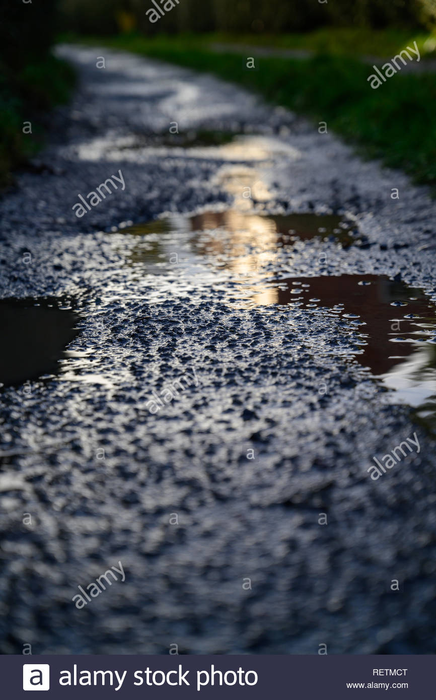 Rempli de pluie de poule créer des flaques dans une piste rugueuse dans le Shropshire après janvier de la pluie. Photo Stock