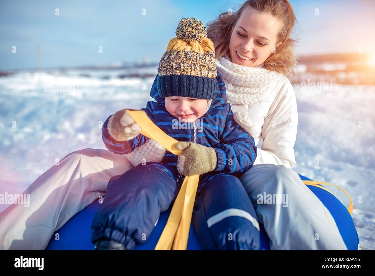 Jeune femme heureuse mère souriant, assis sur tube avec son fils garçon 3-6 ans, jouer à scrabing en hiver. Reste en hiver matin dans la nature. Banque D'Images