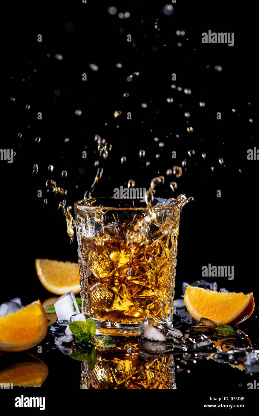 Whisky splash. Verre de whisky décoré de orange, vert menthe et de morceaux de glace. Sur un fond noir avec réflexion, studio shot. Forte alcoho Photo Stock