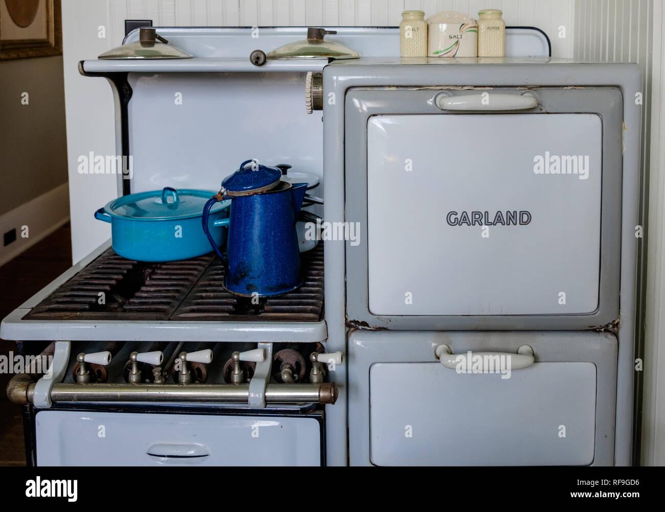 Garland antique cuisinière à gaz 4 brûleurs avec portes en porcelaine blanche et les jambes. Deux bleu et un émail blanc vintage de cuisine. Banque D'Images