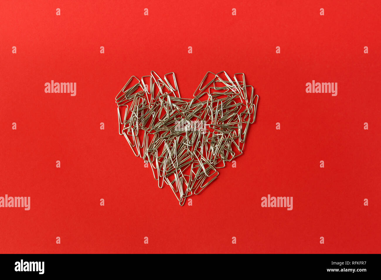 Coeur sur fond rouge. Le jour de la Saint-Valentin. Valentines Day carte de vœux. Coeur de trombones. La papeterie. Photo Stock