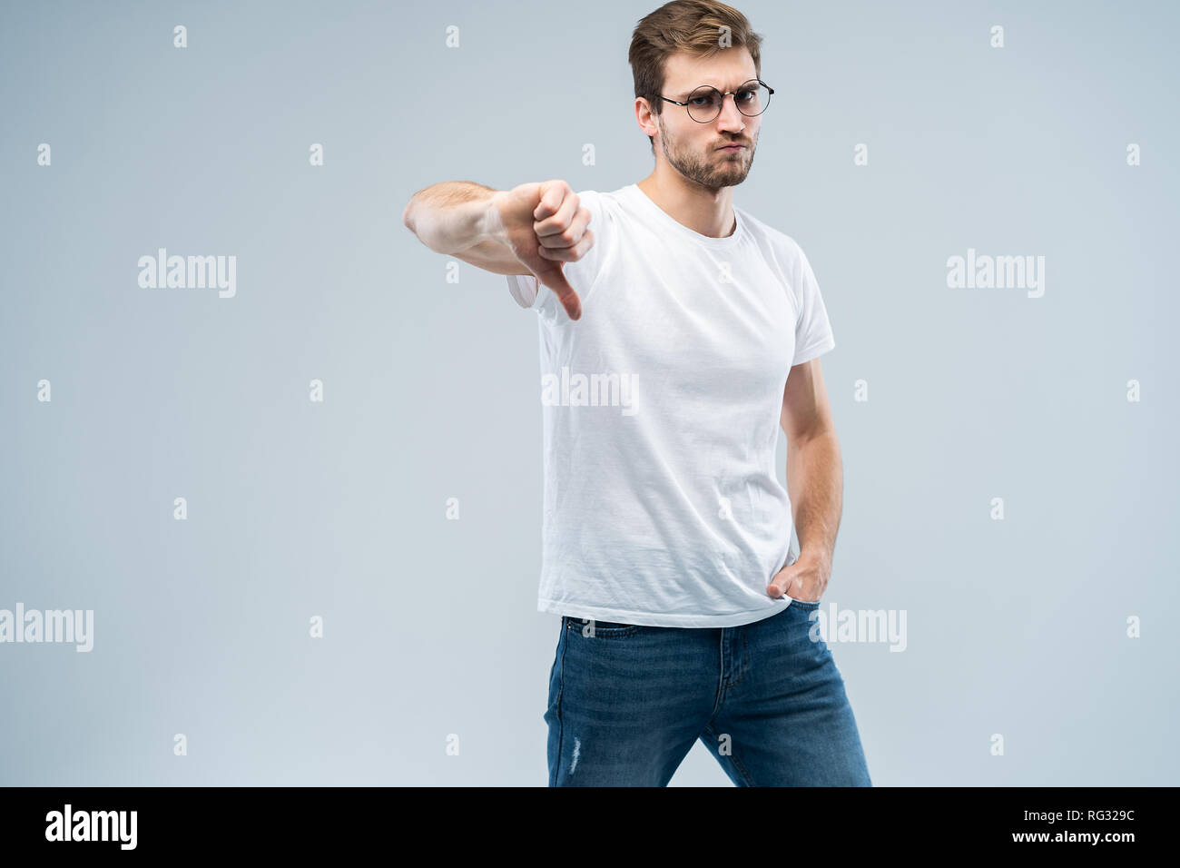 La mode homme élégant à l'intérieur pose contre l'arrière-plan gris, montre des signes d'aversion, ressemble à l'expression négative. Photo Stock
