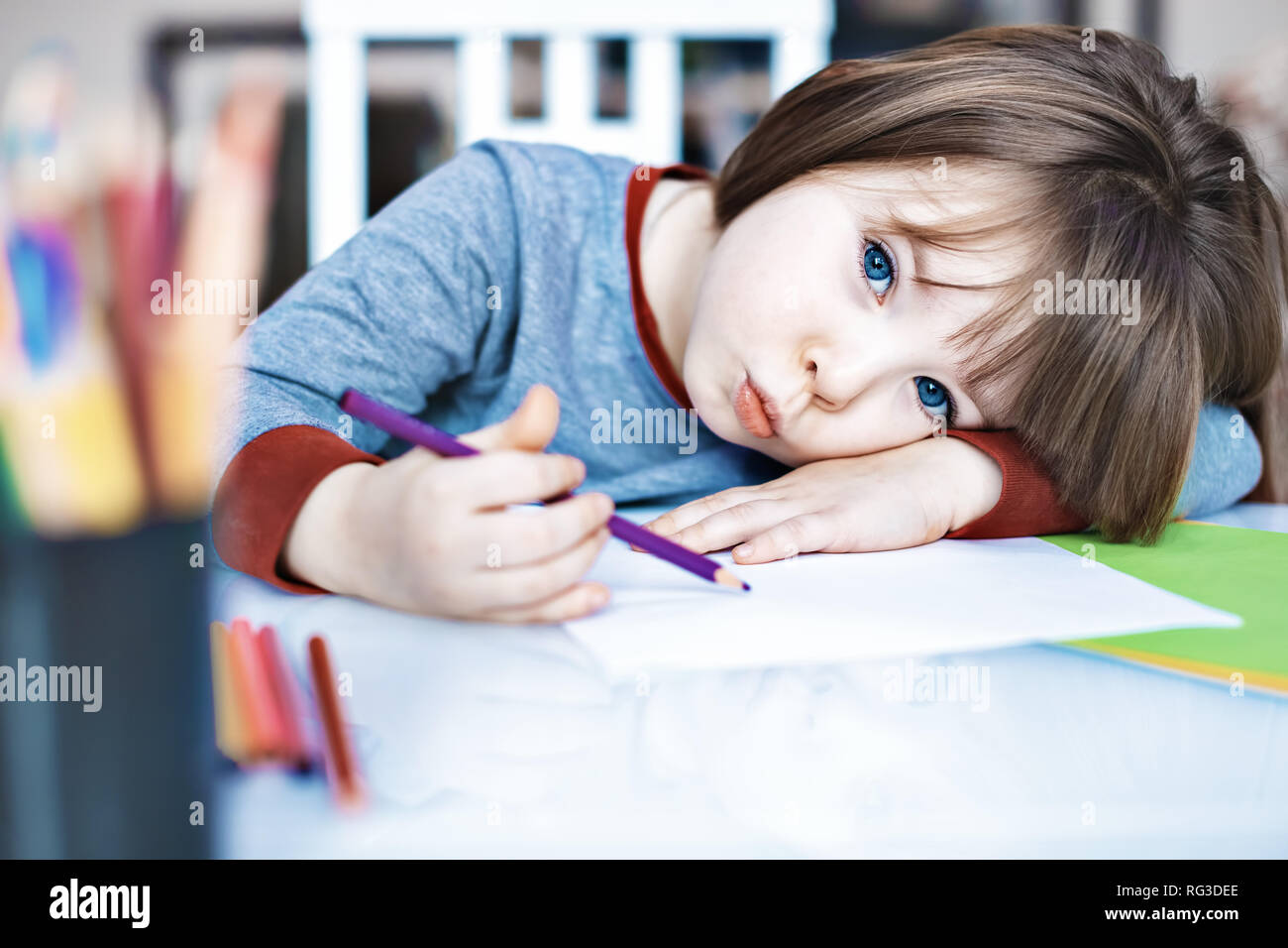 Portrait Kid girl holding siégeant seul au crayon de couleur et à l'ennuie avec visage, enfant d'âge préscolaire portant la tête en bas, sur table avec visage triste Banque D'Images