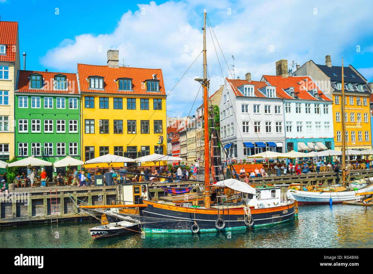Vue panoramique sur Nyhavn avec des bateaux par un remblai en plein soleil, les gens marcher et s'asseoir dans les restaurants, Copenhague, Danemark Banque D'Images