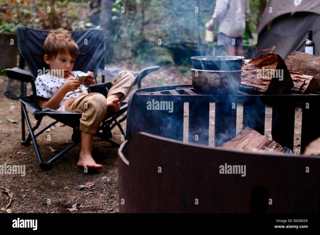 Une jeune fille se trouve près d'un feu de camp, Fern télévision camping area, Eungella National Park, Queensland, Australie Banque D'Images