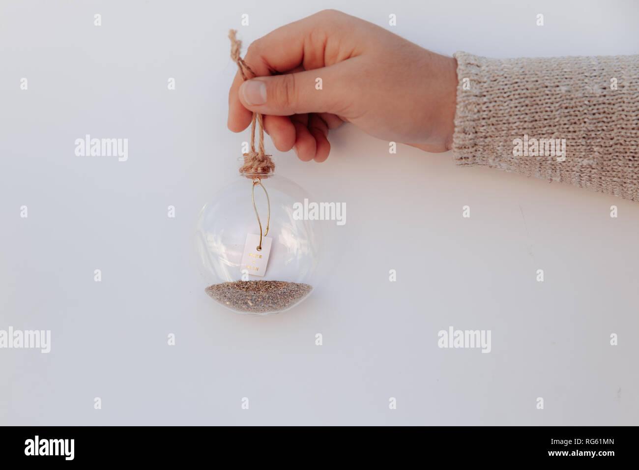 Girl's hand holding a glass bauble avec un message make a wish Banque D'Images