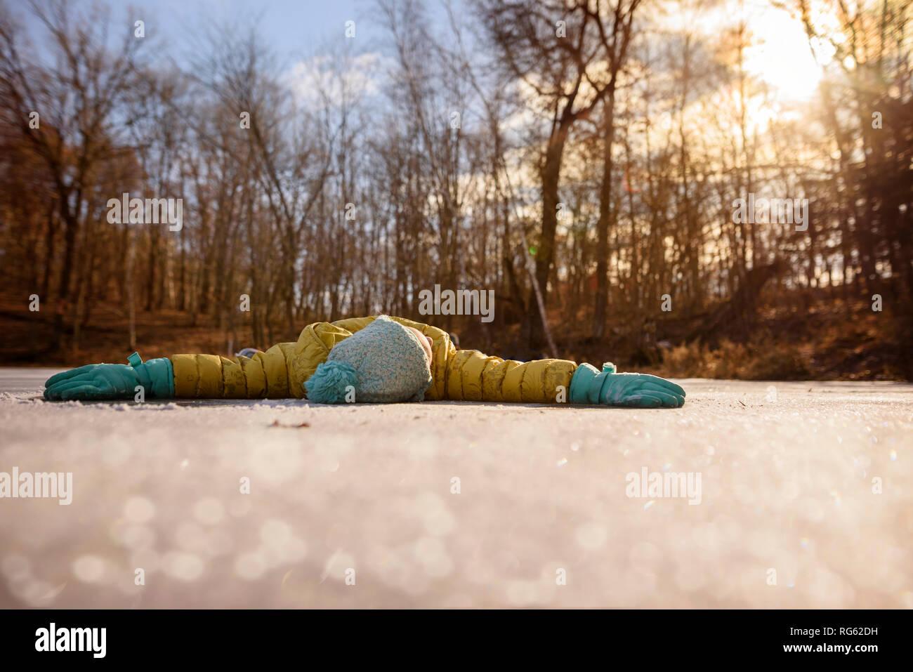 Fille couchée sur un étang gelé avec ses bras tendus, United States Banque D'Images