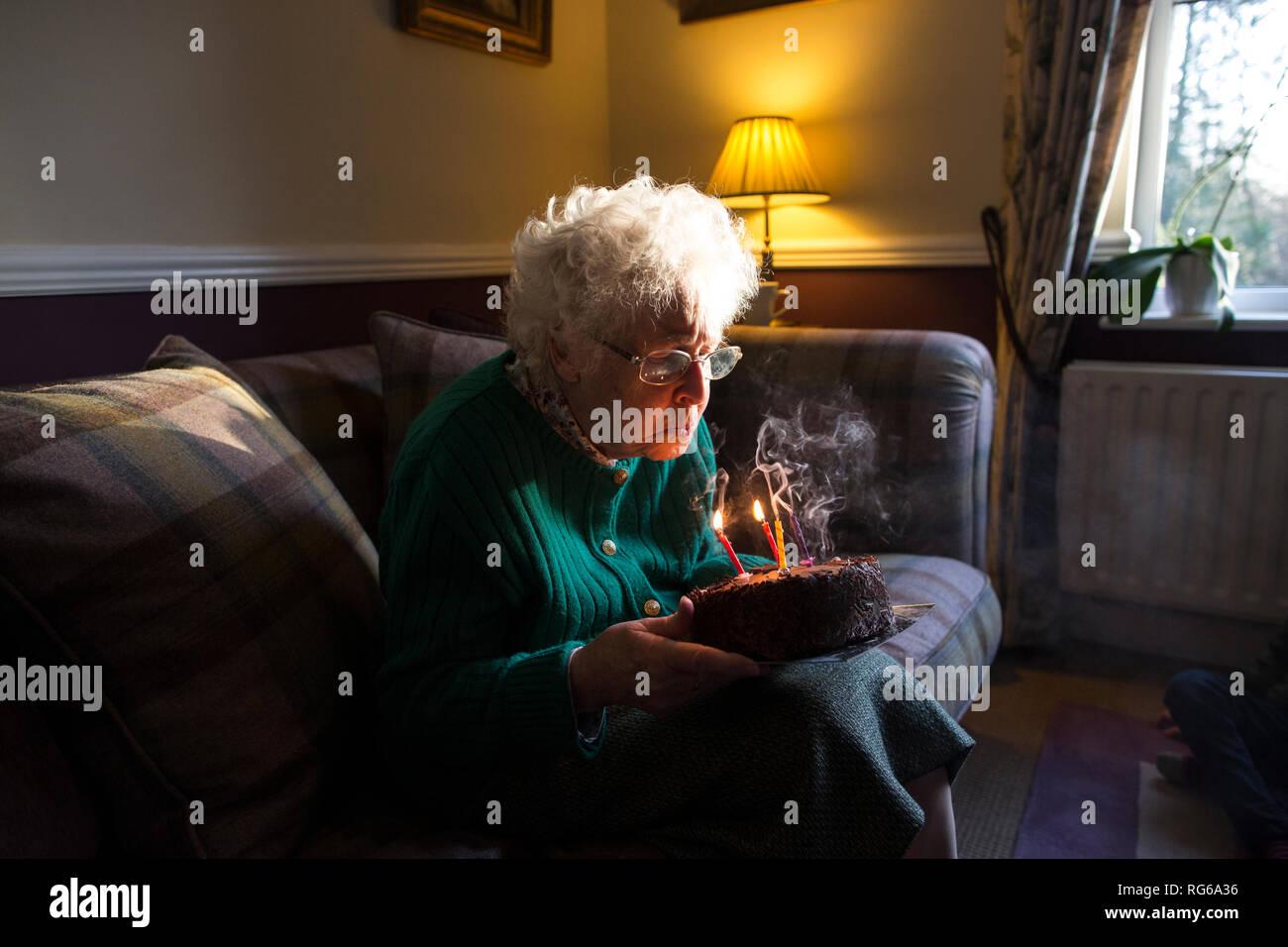 Vieille Femme célèbre son anniversaire avec un gâteau tout en soufflant les bougies, Angleterre, Royaume-Uni Photo Stock