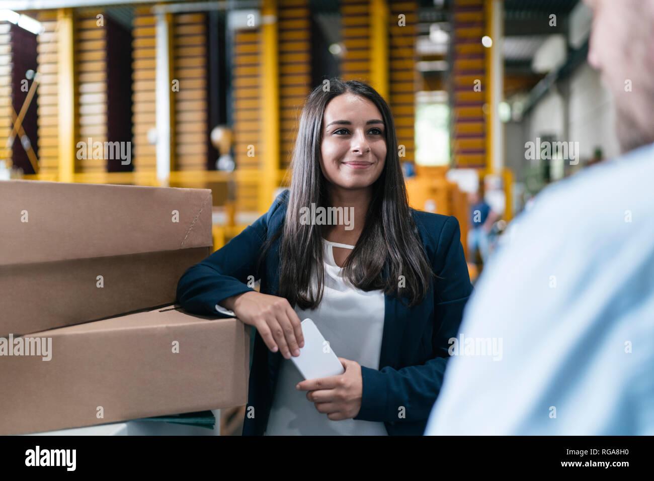 Jeune femme travaillant dans l'entrepôt de distribution, parler aux collègue Photo Stock