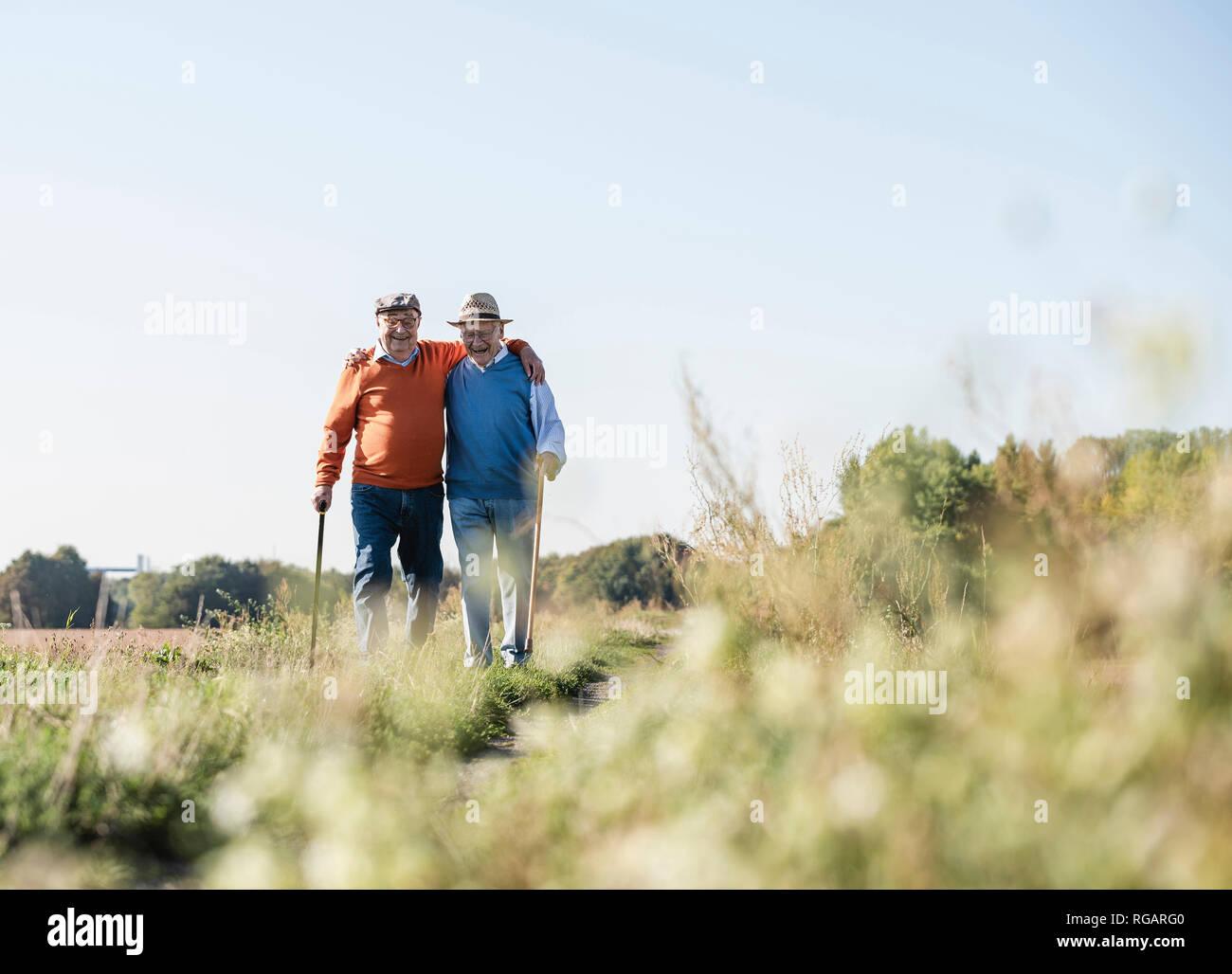 Deux vieux amis de prendre une promenade à travers les champs, en parlant de vieux temps Photo Stock
