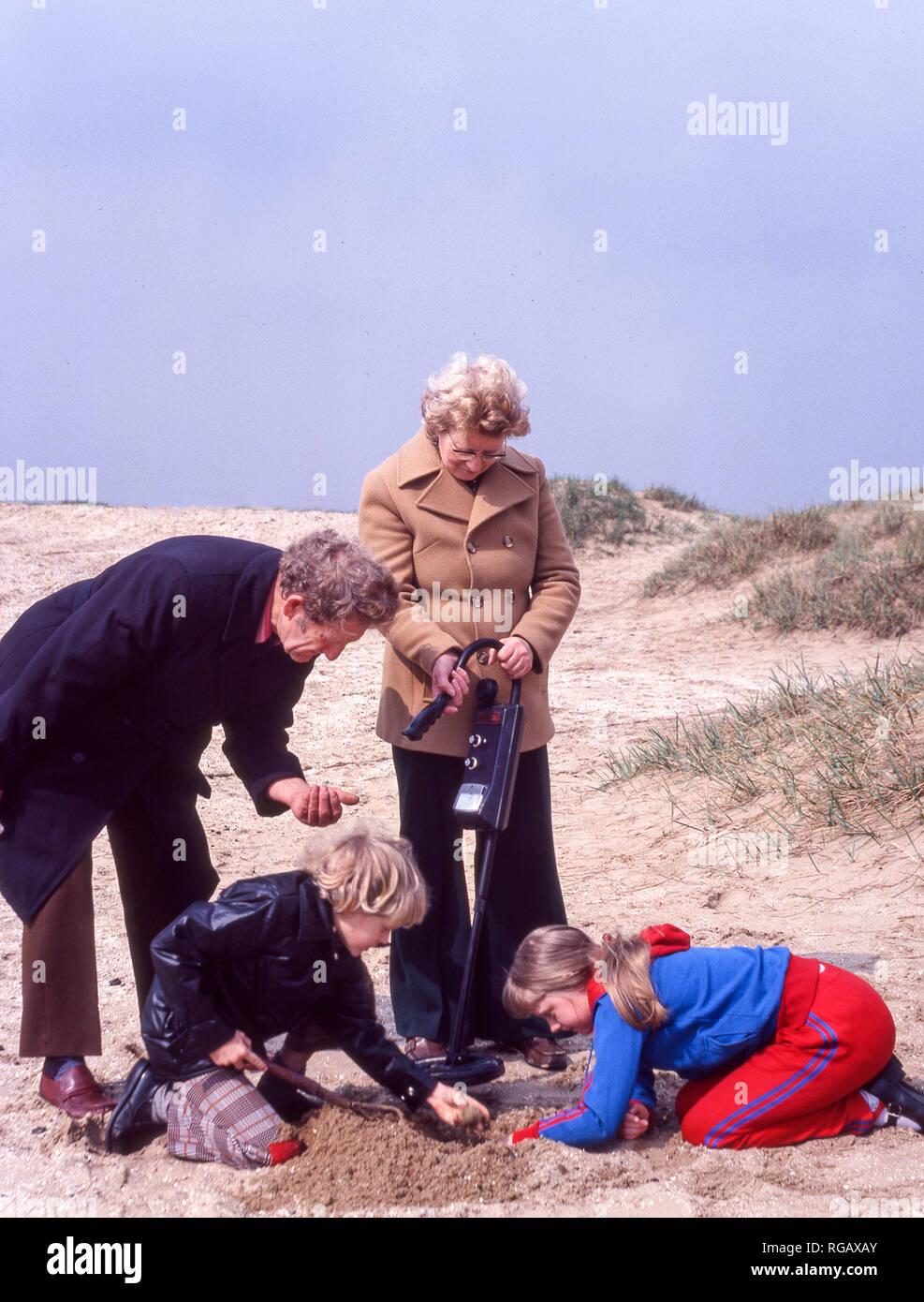 Les grands-parents avec deux petits-enfants à l'aide d'un détecteur de métal sur une plage dans le nord-ouest de l'Angleterre. Banque D'Images