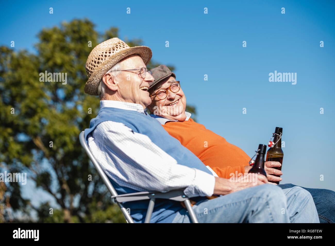 Deux vieux amis assis dans les champs, la consommation de bière, en parlant de vieux temps Photo Stock