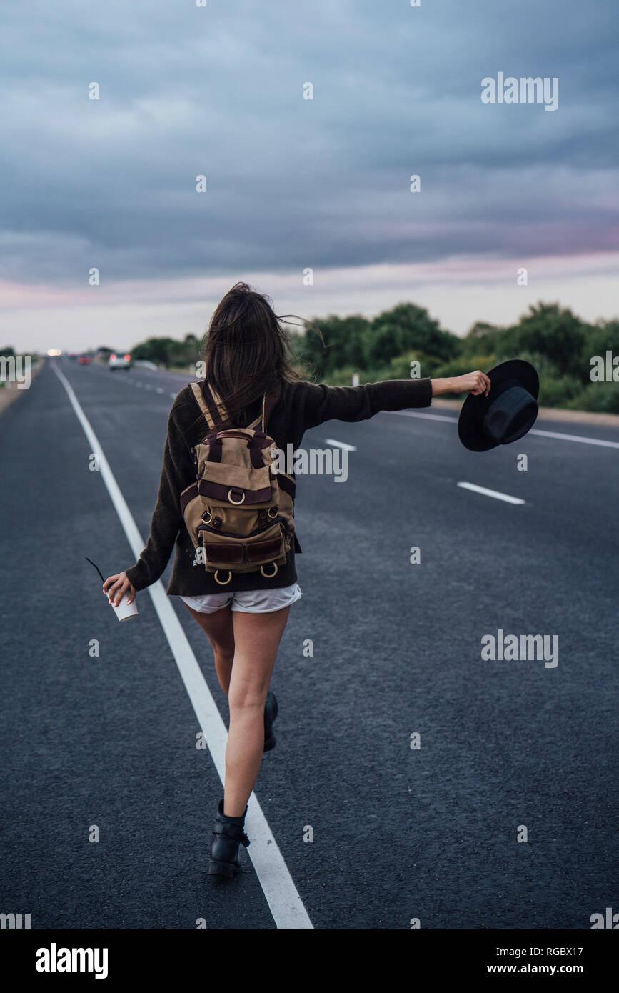 Vue arrière de l'auto-stop jeune femme avec sac à dos et boissons debout à la ligne latérale Banque D'Images