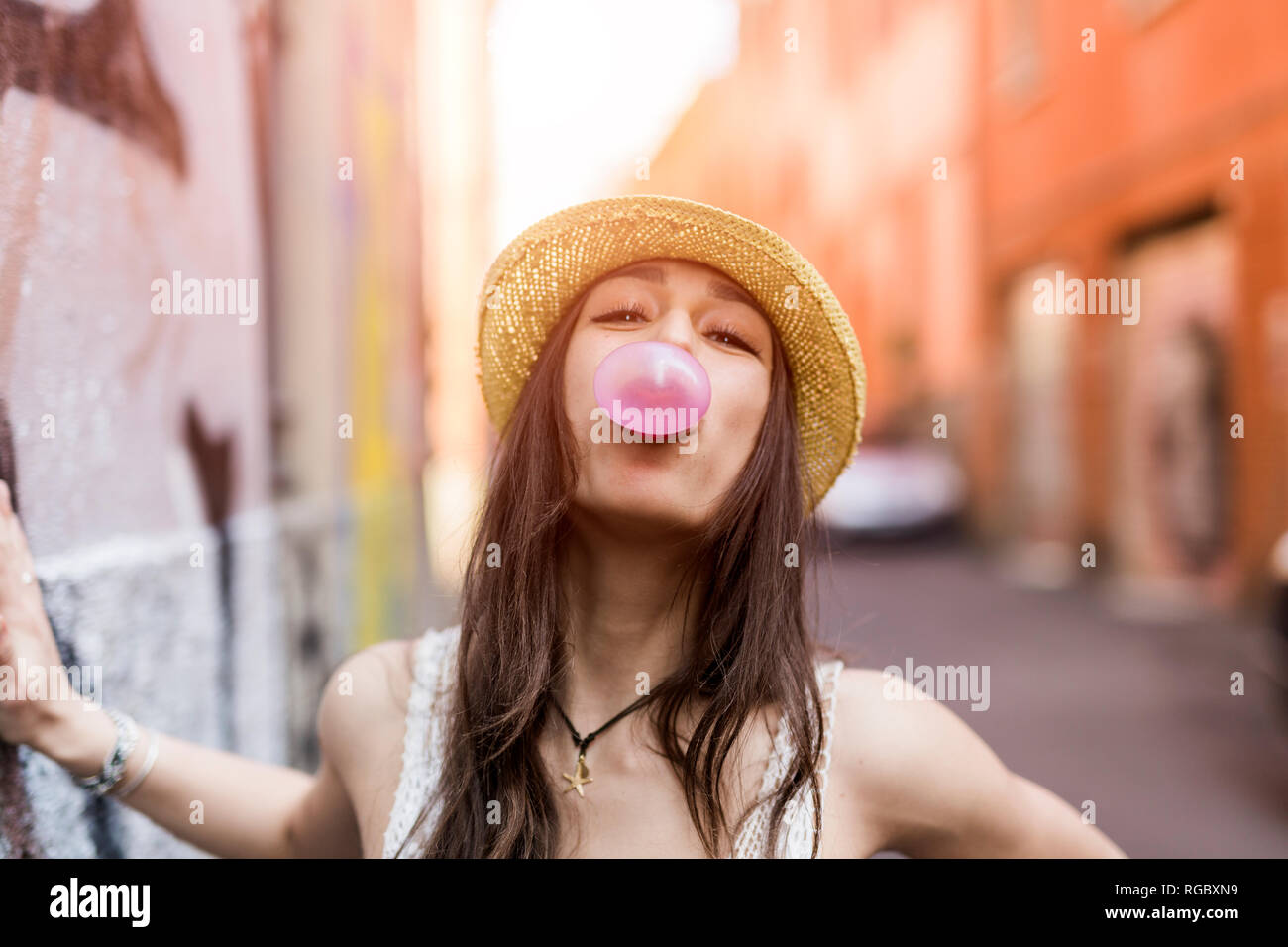 Portrait of young woman blowing bubble gum rose Photo Stock