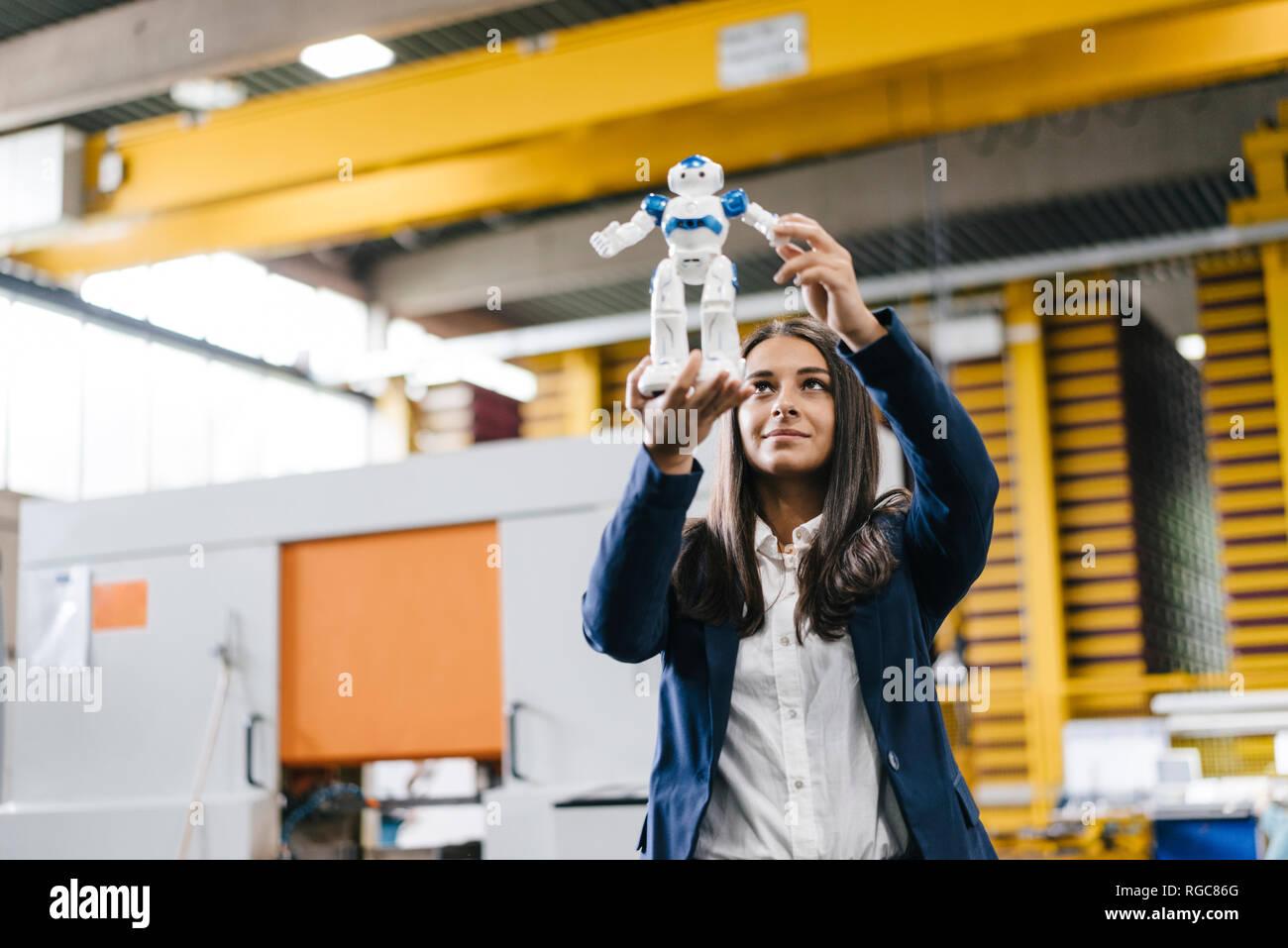 Jeune femme travaillant dans l'entrepôt de distribution, en regardant toy robot Photo Stock