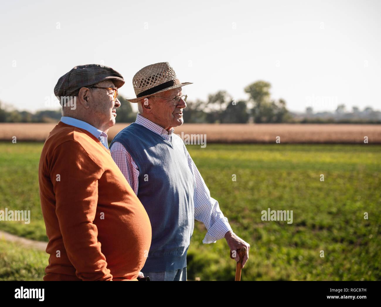 Deux vieux amis debout dans les champs, en parlant de vieux temps Photo Stock