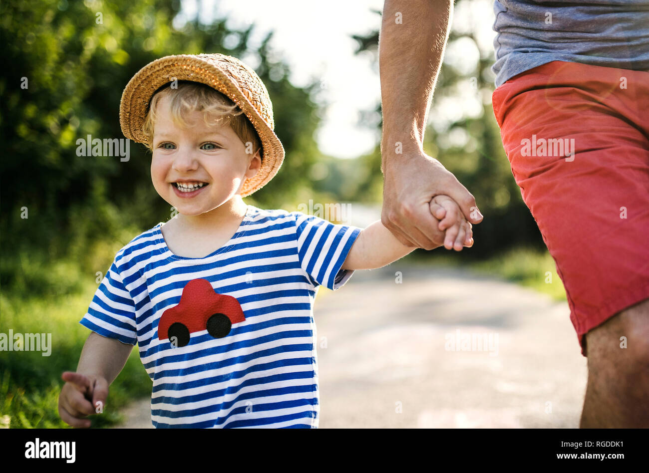 Portrait of laughing toddler marche sur main du père Banque D'Images
