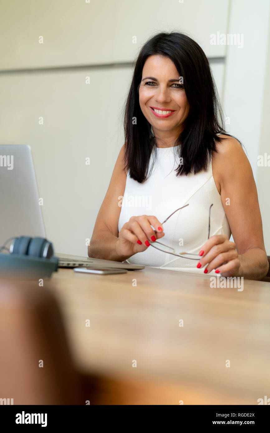 Portrait of smiling dark-haired woman using laptop at desk Banque D'Images