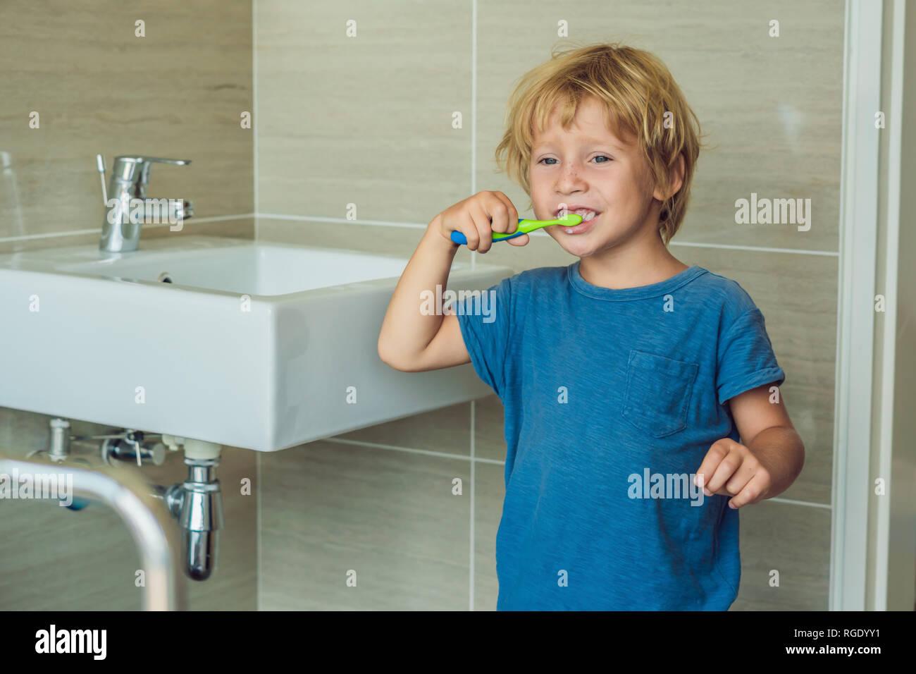 Petite blonde boy learning se brosser les dents dans la baignoire. Kid apprendre à rester en bonne santé. Concept de soins de santé Banque D'Images
