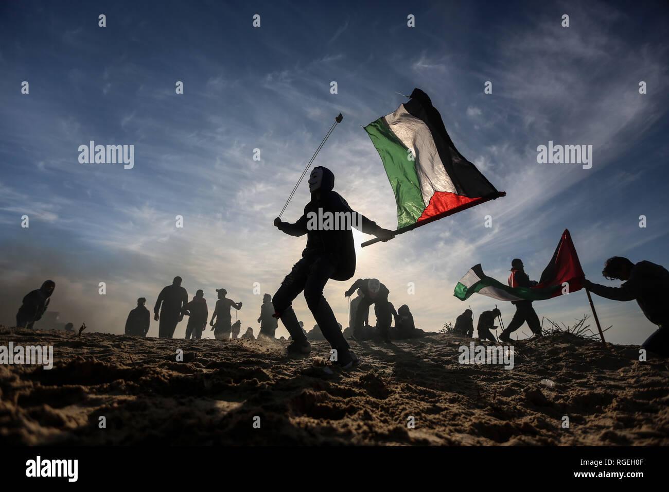 La bande de Gaza. 29 janvier, 2019. Un manifestant palestinien utilise une fronde pour lancer des pierres sur des soldats israéliens lors d'affrontements près de la frontière avec Israël, dans le nord de la bande de Gaza, le 29 janvier 2009, 2019. Au moins 15 Palestiniens ont été blessés par balles mardi après-midi par des tirs de soldats israéliens lors d'affrontements qui ont éclaté au nord de la bande de Gaza, près de la frontière avec Israël, a déclaré que les infirmiers. Credit: Stringer/Xinhua/Alamy Live News Photo Stock