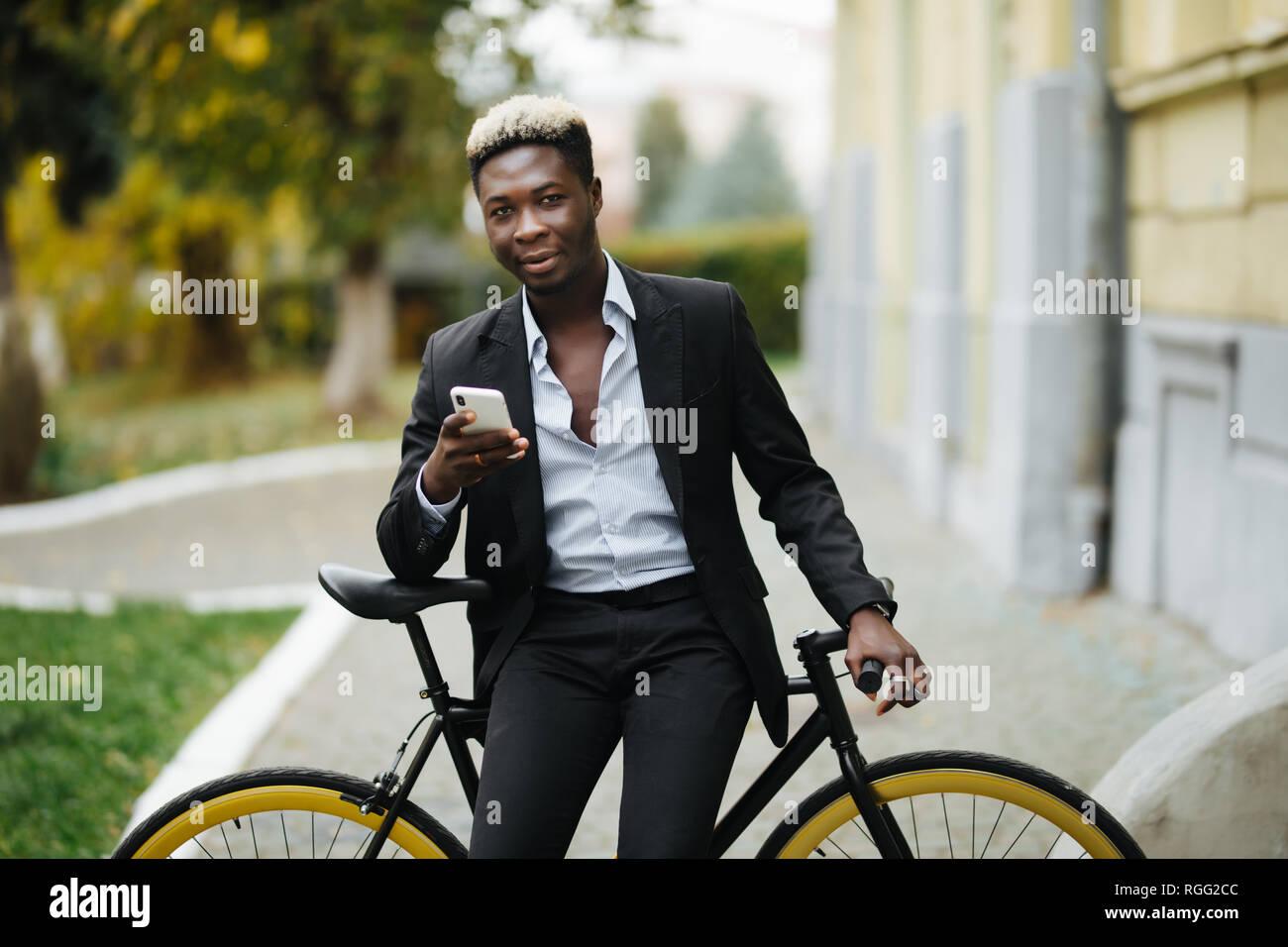 Homme Hipster avec location de l'envoi de message sur téléphone mobile en milieu urbain ville Banque D'Images