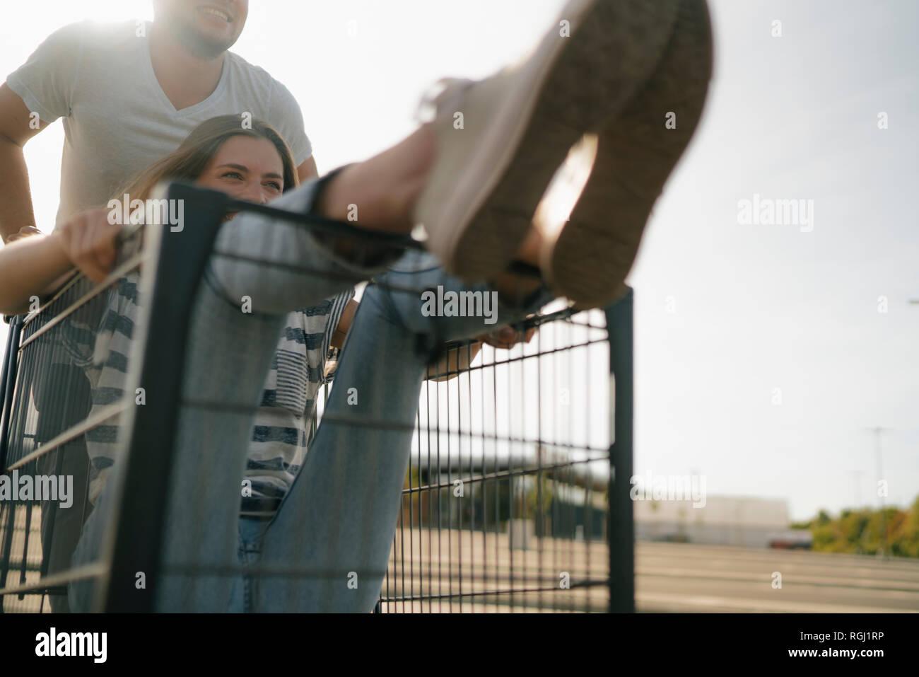 Jeune homme insouciant poussant copine dans un panier Banque D'Images
