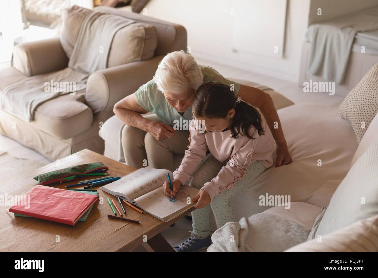 Vue latérale d'une grand-mère d'aider sa petite-fille à faire ses devoirs dans la salle de séjour à la maison Banque D'Images