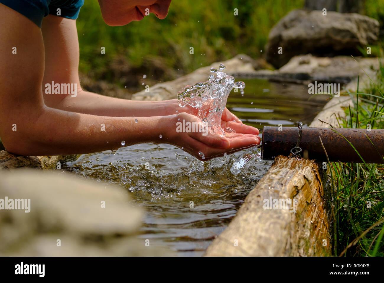 L'Allemagne, la Haute-Bavière, Chiemgau, jeune homme à la fontaine rafraîchissante Banque D'Images