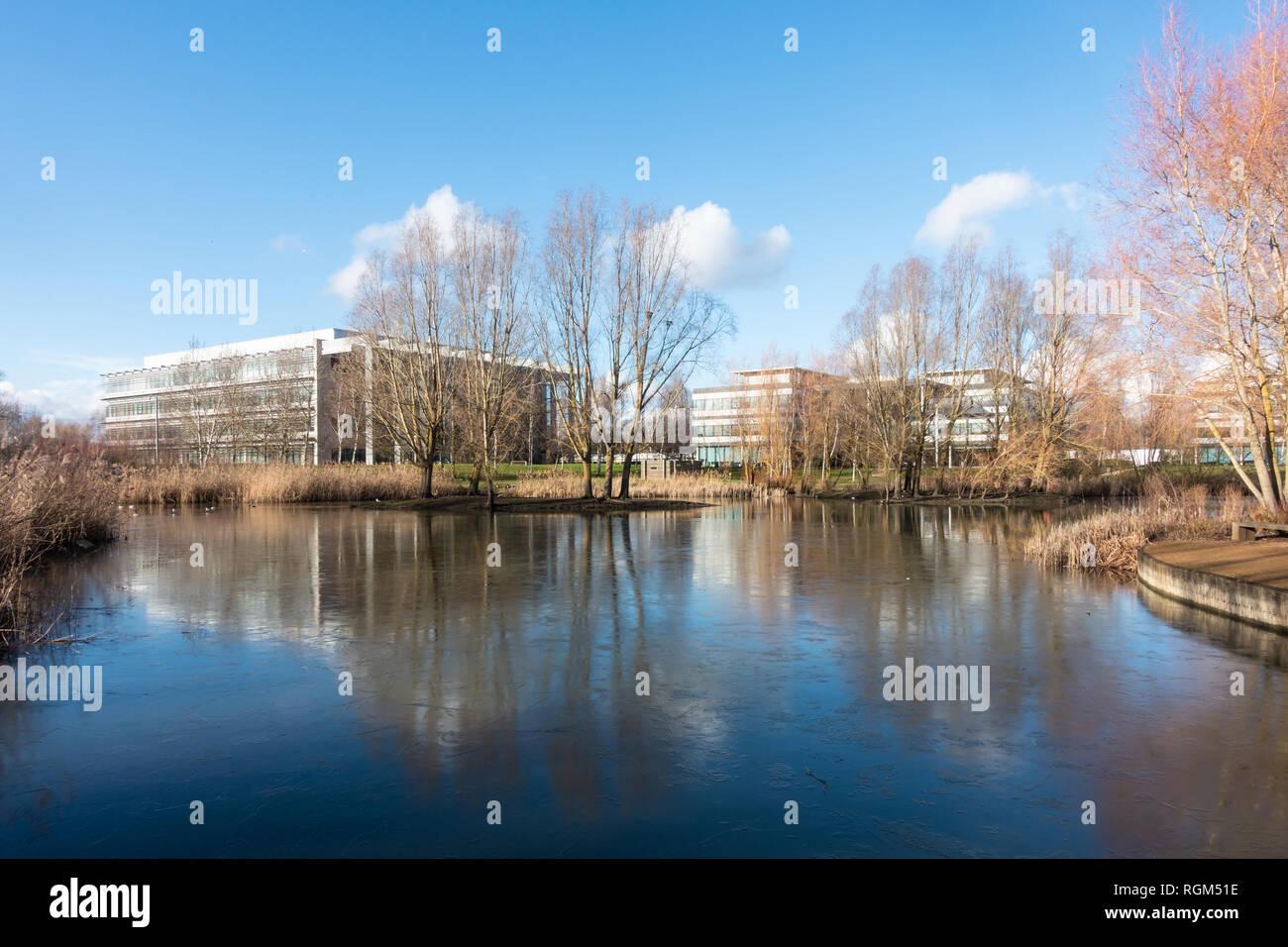 Bleu ciel et les édifices reflètent dans un lac gelé dans le centre d'un parc d'affaires en hiver. Banque D'Images