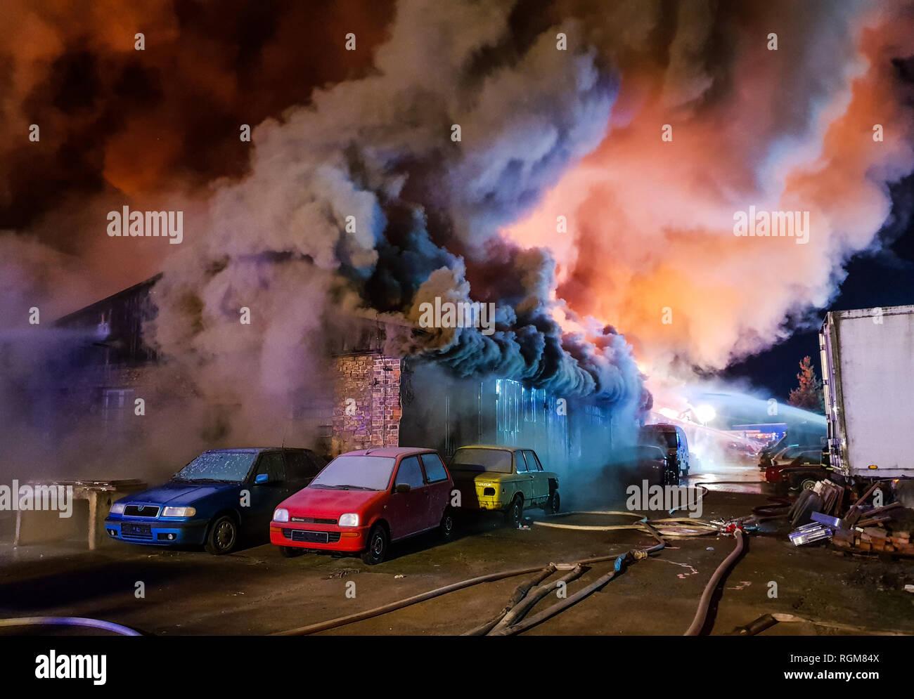 Zeuthen, Allemagne. 30Th Jan, 2019. Une fumée dense se dégage sous le toit d'un entrepôt en feu. Plus de 100 pompiers ont travaillé d'éteindre le grand incendie. Credit: Julian Stähle/dpa/Alamy Live News Photo Stock